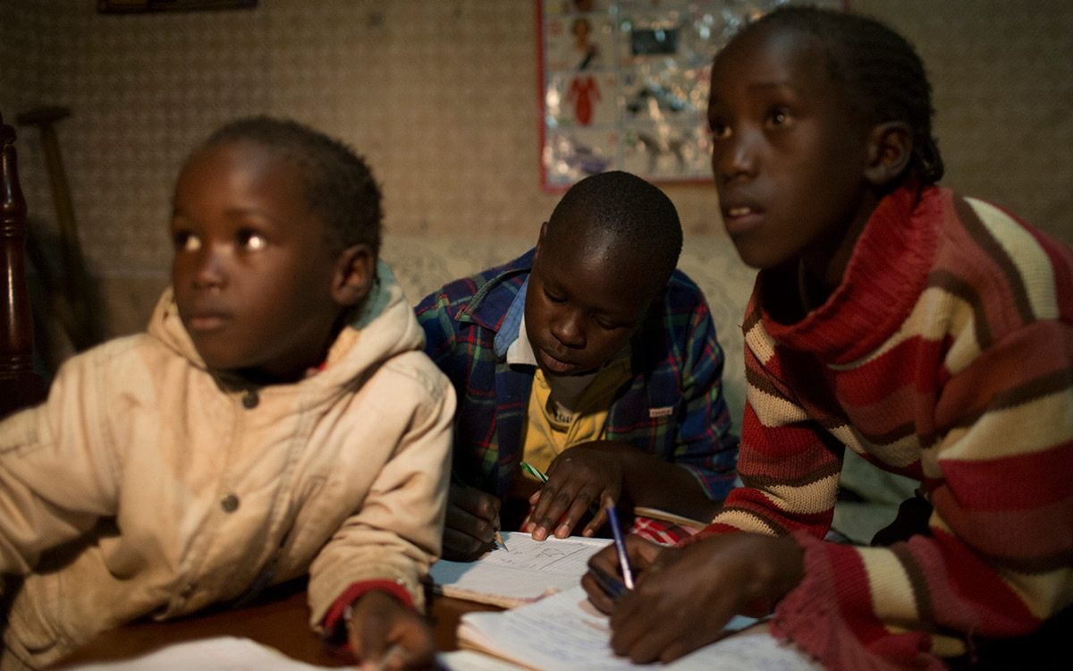 Rosemarie, Alice und Precious do their homework by the light of the solar-powered lamp.