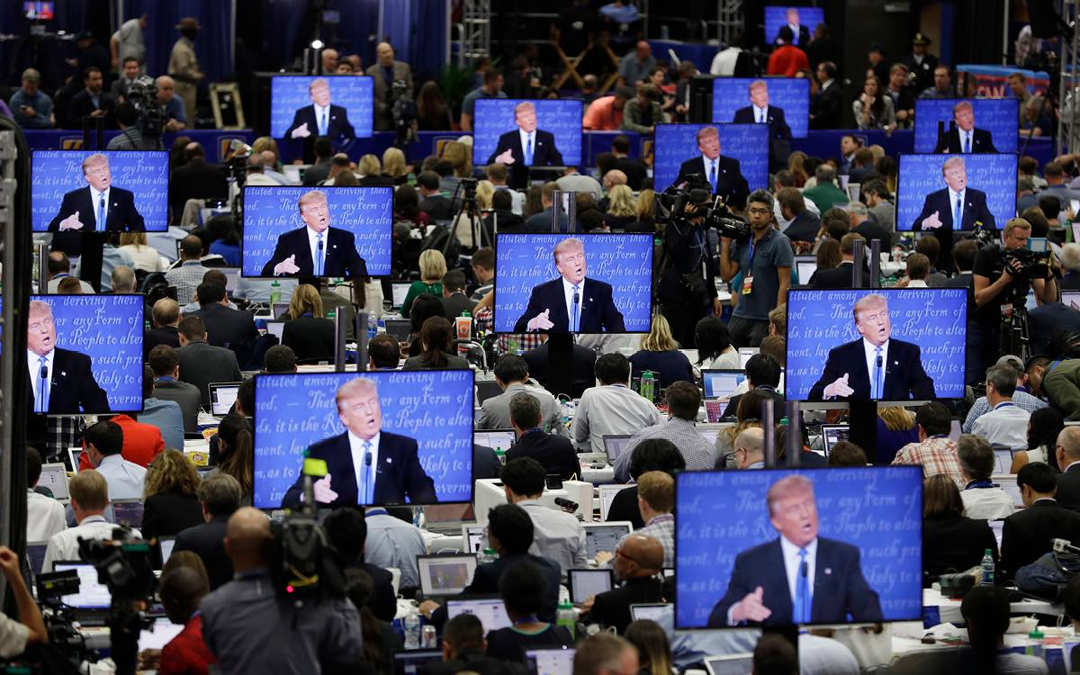 Journalists in a media center follow Donald Trump at an election rally.